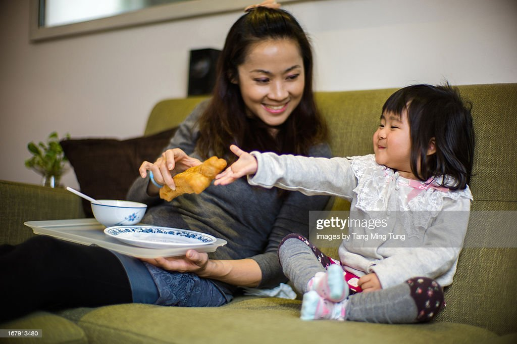 Young mom and toddler having breakfast : Stock Photo