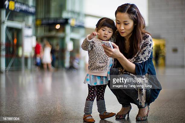 Young mom and toddler having fun using smartphone