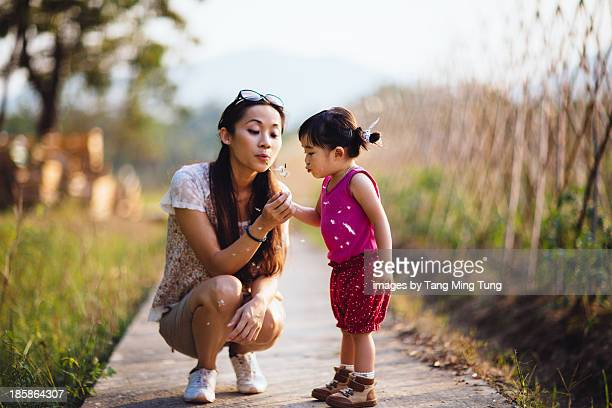 Young mom blowing dandelion with toddler girl