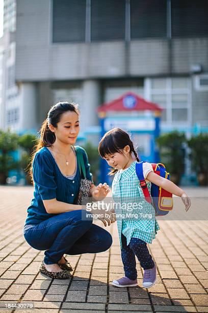 Young mom bringing toddler to school joyfully