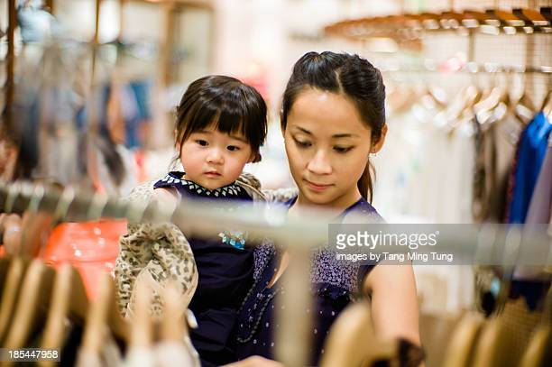 Young mom choosing clothes with toddler girl