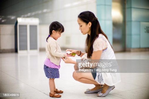 Young mom cleaning toddler's hand with sanitizers