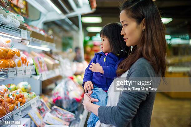 Young mom doing grocery shopping with toddler girl