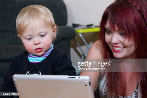 Young mom entertaining daughter on pad computer : Stock Photo