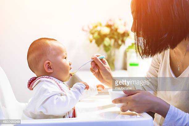 Young mom feeding her kid