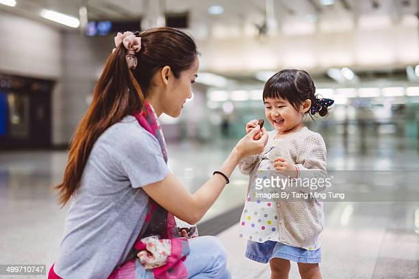 Young mom giving snacks to little girl