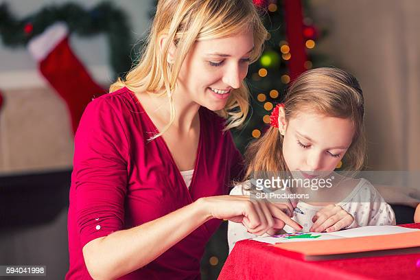 Young mom helping daughter make Christmas greeting cards