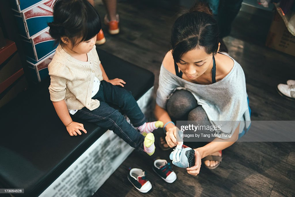 Young mom helping toddler fitting with new shoes : Stock Photo