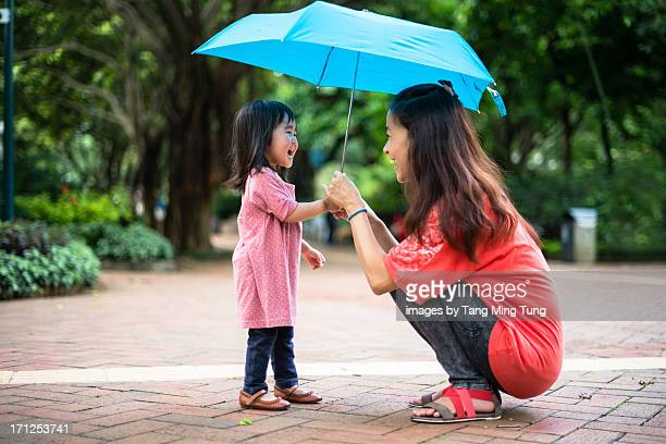 Young mom holding an umbrella with toddler girl