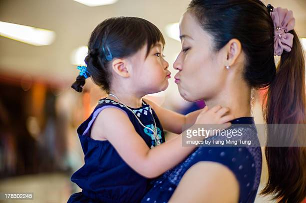 Young mom holding and kissing toddler girl