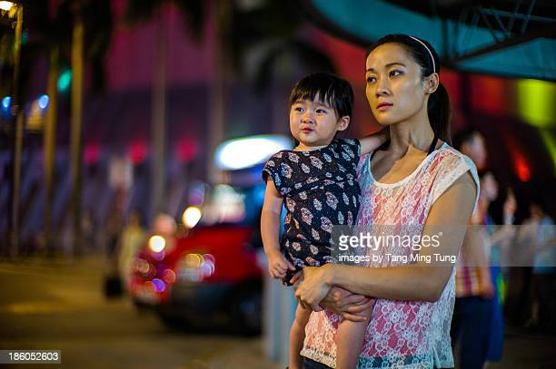 Young mom holding toddler girl on street at night