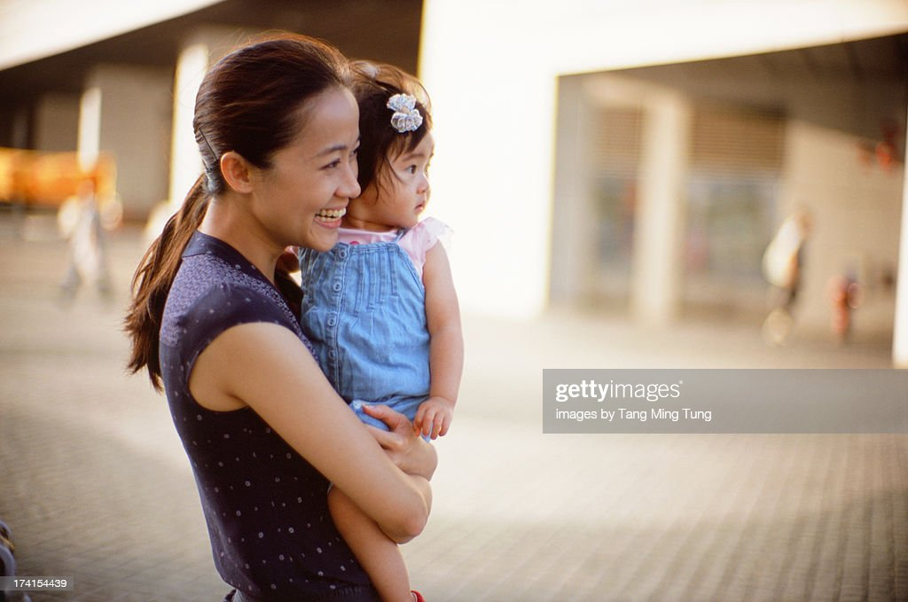 Young mom holding toddler girl smiling : Stock Photo