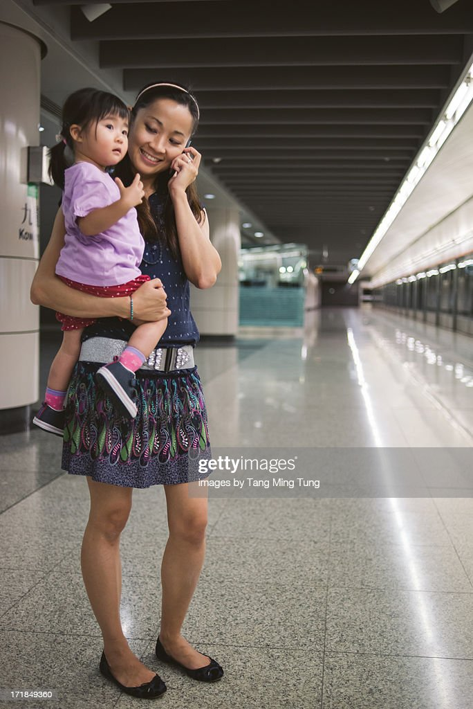 Young mom holding toddler talking on smartphone : Stock Photo