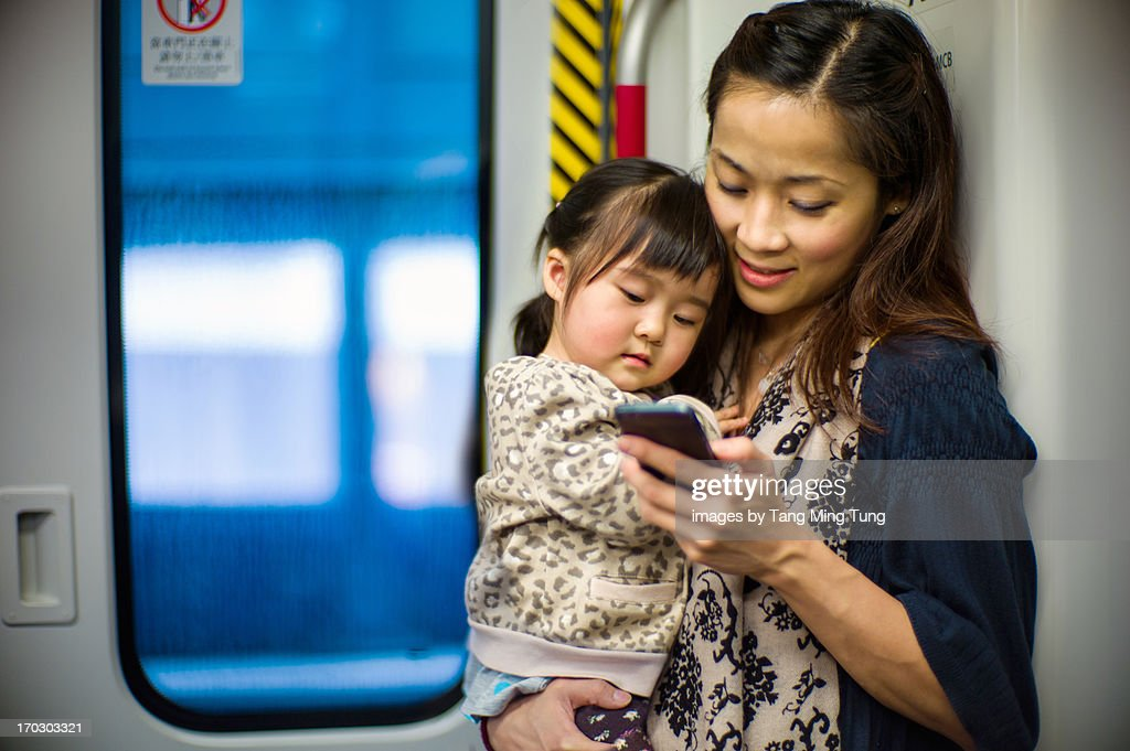 Young mom holding toddler using a smartphone : Stock Photo