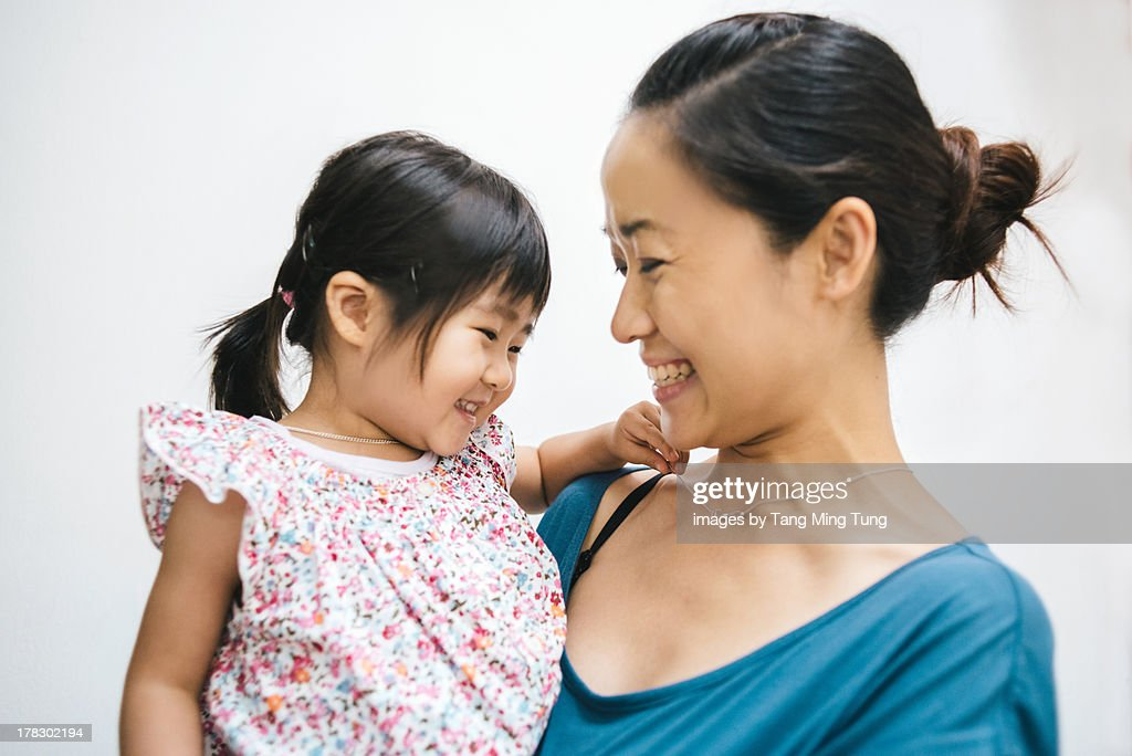Young mom holding toddler with love and affection