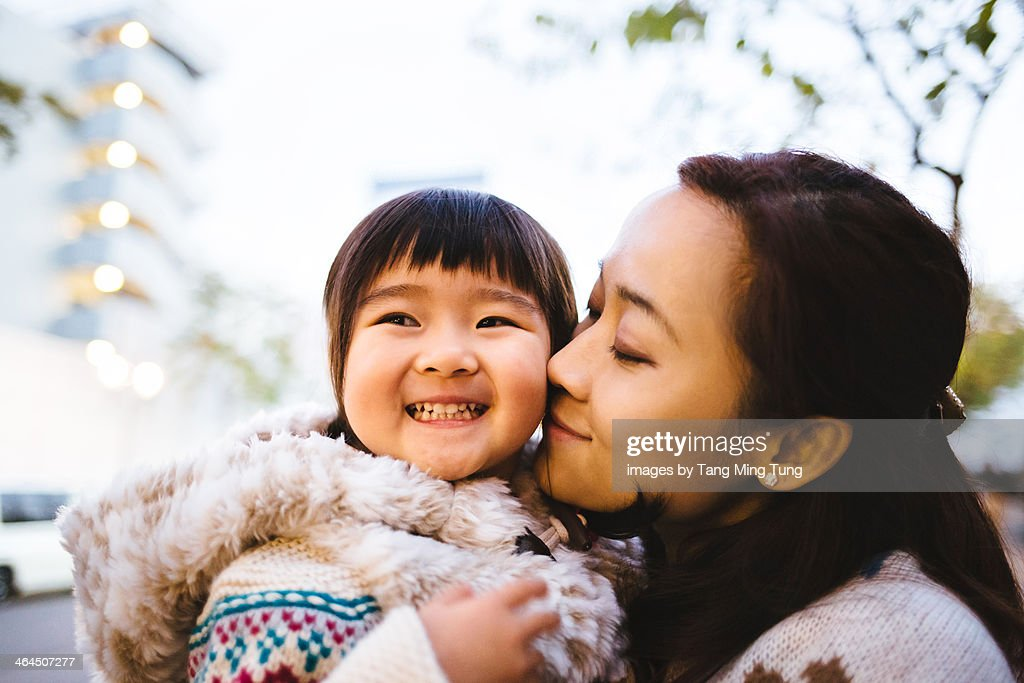 Young mom kissing toddler girl's cheek : Stock Photo