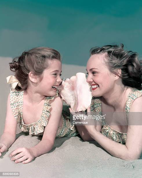 Young mom laying on the beach with daugther listening to conch shell Los Angeles California 1950s