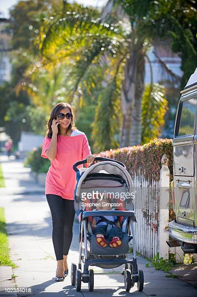 young Mom on phone taking her baby for awalk