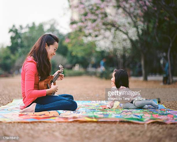 Young mom playing ukulele for toddler on lawn