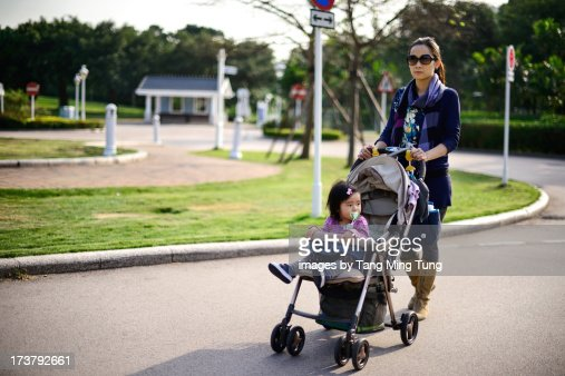 Young mom pushing baby in stroller