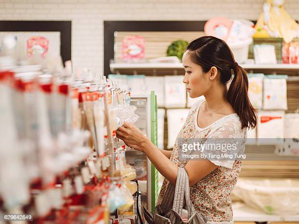 Young mom shopping accessories at department store
