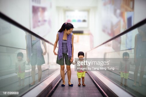 Young mom standing on escalator with toddler girl