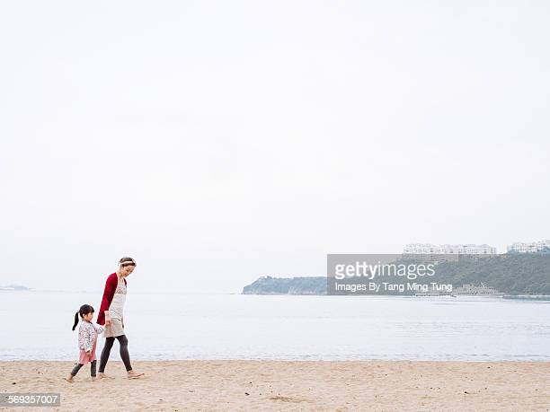 Young mom strolling on beach with daughter