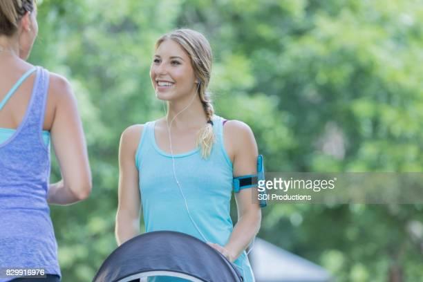 Jeune maman s'entretient avec un ami en se promenant dans le parc