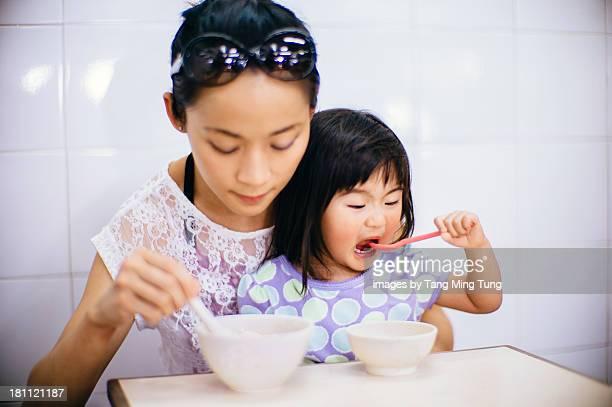 Young mom & toddler girl having rice porridge