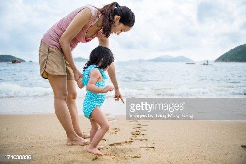 Young mom & toddler having fun at beach