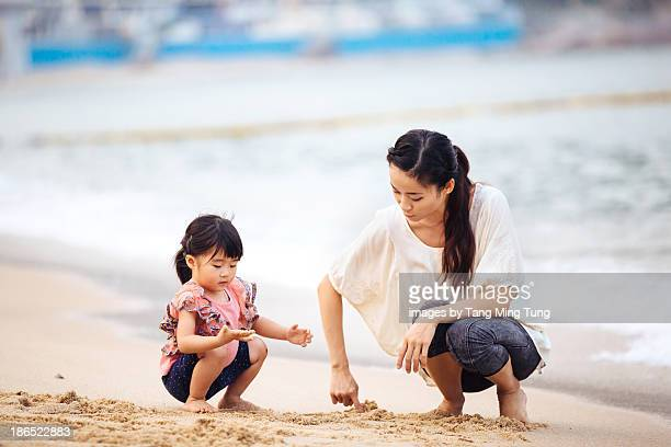 Young mom & toddler playing on beach joyfully