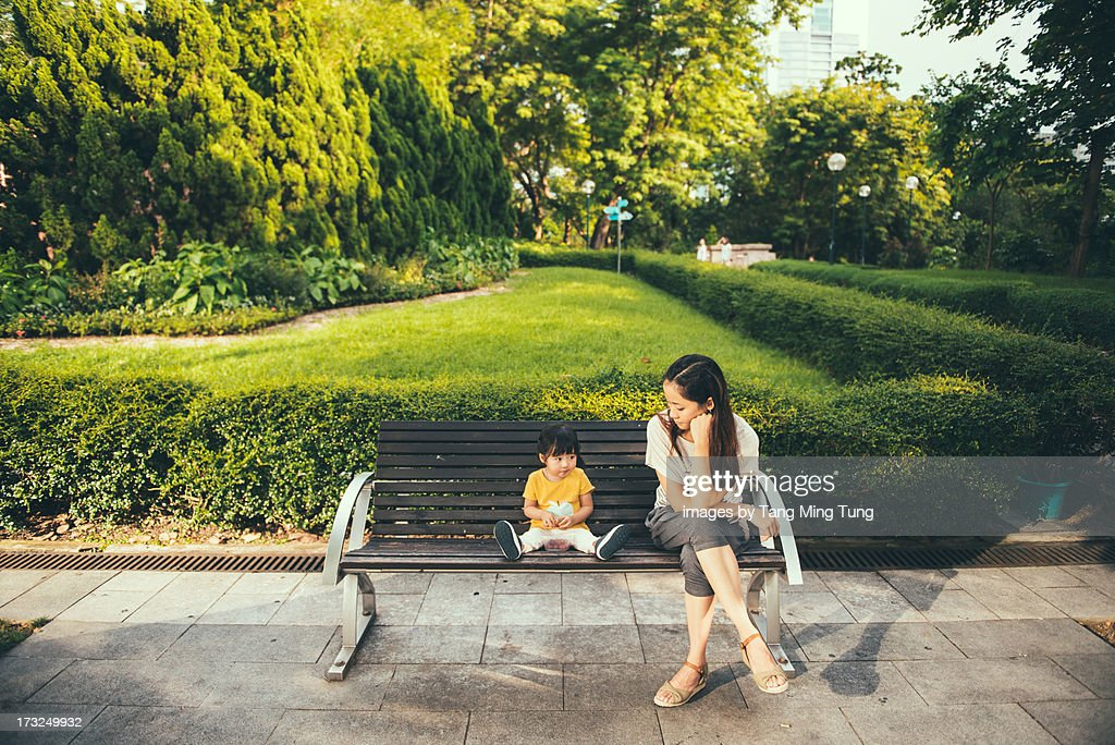 Young mom & toddler sitting and relaxing on bench : Stock Photo
