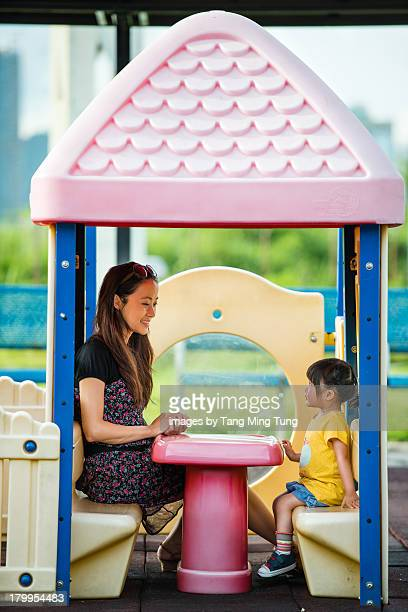 Young mom & toddler sitting in toy house