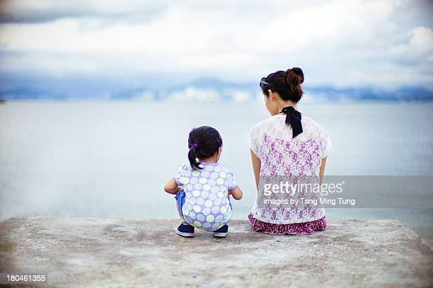 Young mom & toddler sitting on dock looking at sea