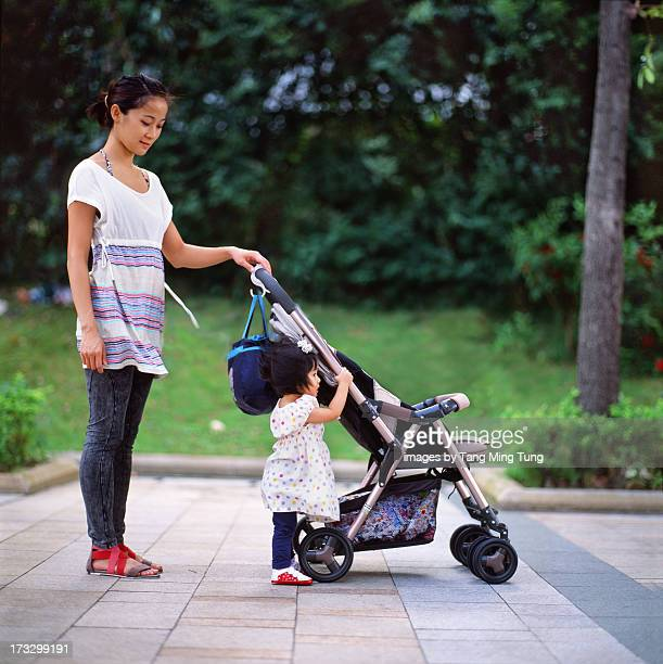 Young mom & toddler strolling in park