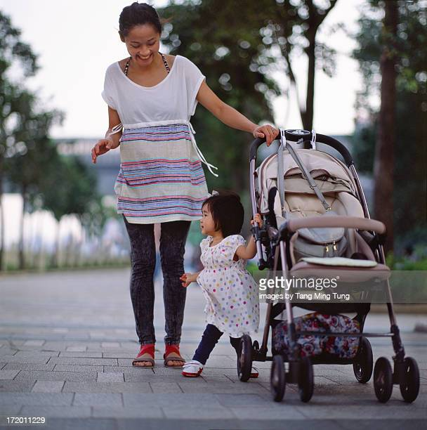 Young mom & toddler strolling in the park joyfully