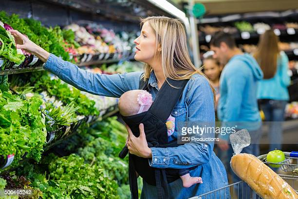 Young mom wearing baby in carrier while shopping for produce