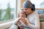 A beautiful young ethnic woman with cancer holds her preschool-age daughter in her lap by their living window. They are holding and playing with a little plastic toy and mom is smiling. She is also we