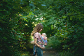 Young Mom carrying her daughter in a sling during their outdoor walk.