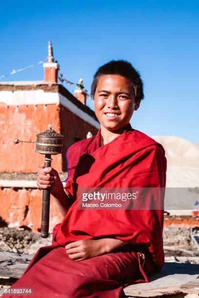 Young monk spinning prayer wheel, Upper Mustang, Nepal