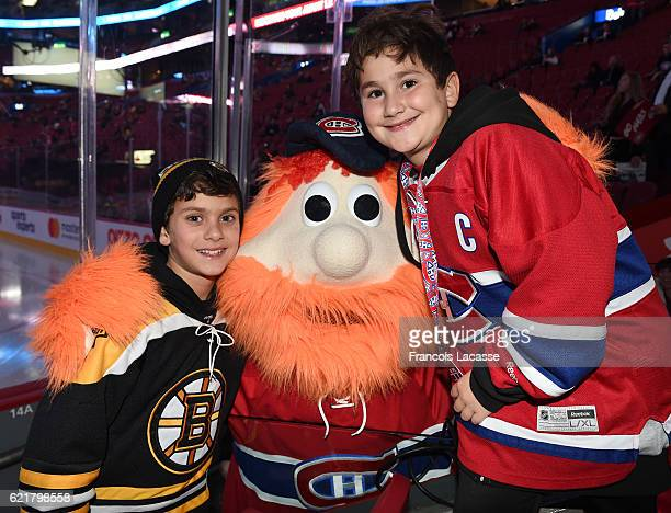 Young Montreal Canadiens and Boston Bruins fans pose with Youppi prior the NHL game at the Bell Centre on November 8 2016 in Montreal Quebec Canada