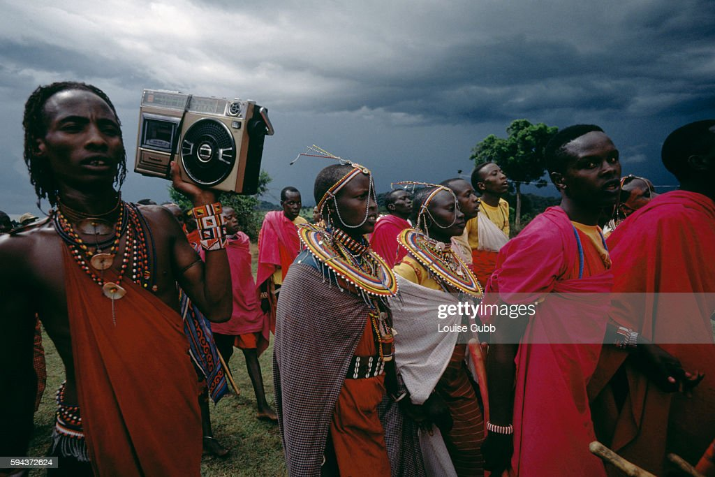 A young Moran warrior holds a tape recorder while his relatives join in the parade and sing songs during the Masai Eunoto ceremony