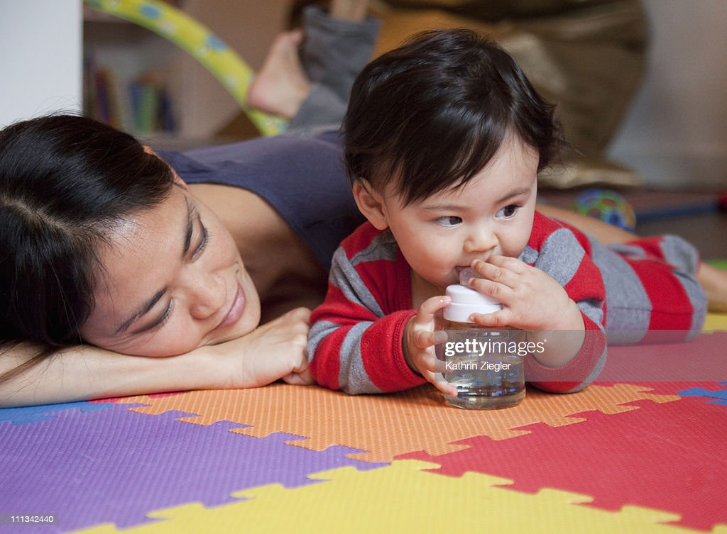 young mother and baby boy cuddling on the floor : Stock Photo