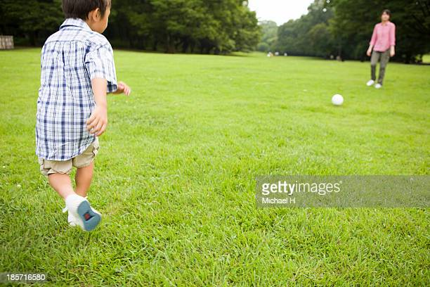 young mother and child playing soccer in the park