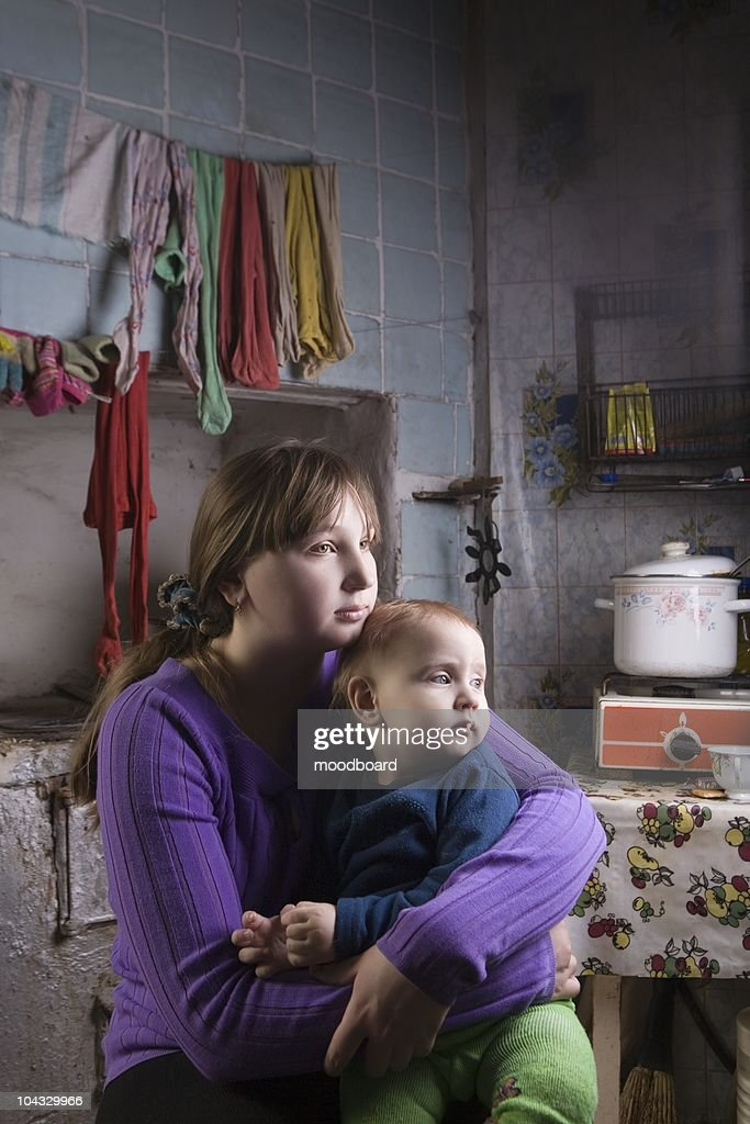 Young mother and child sit in kitchen interior : Stock Photo