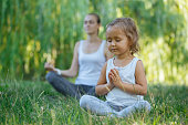 Young mother and cute little daughter meditating in lotus pose together at green summer park.