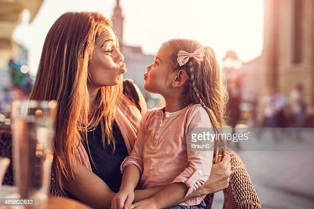 Jeune mère et sa fille ensemble en plein air tout en profitant de l'apparition de plis.