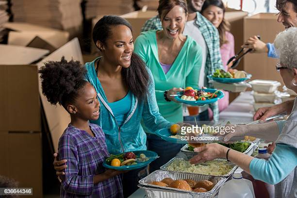 Young mother and daughter receive meal in soup kitchen