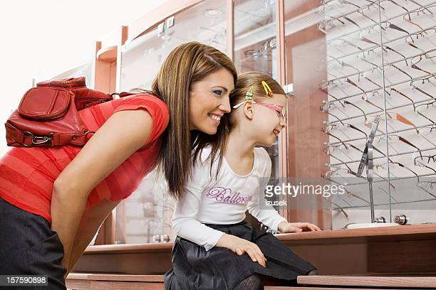Young Mother And Daughter Shopping For New Glasses