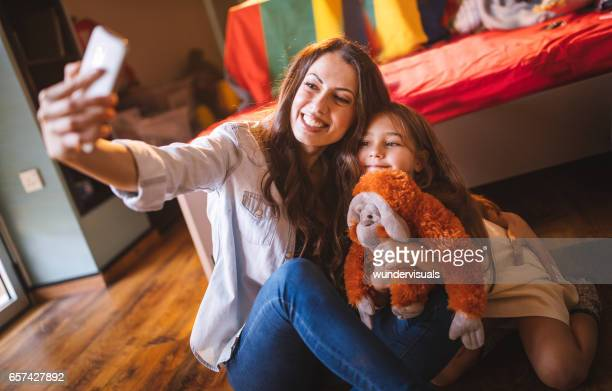 Young mother and daughter taking a selfie and photo-messaging dad